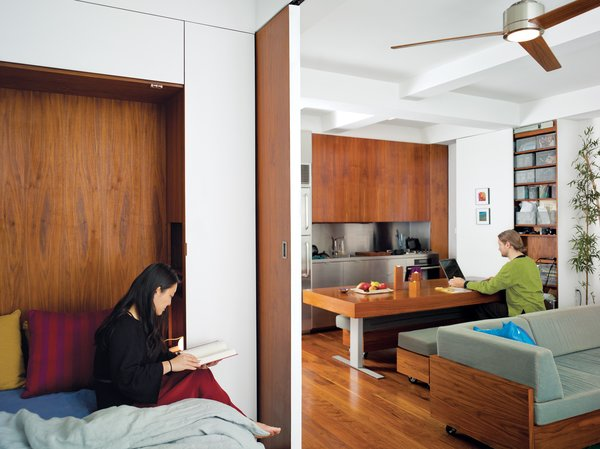 "Screened by the sliding door, Rosa cozies up with a book in the bedroom, while across the apartment Robert uses the hydraulic kitchen table as a work desk. ""We wanted to explore the power of custom design by creating integrated furniture to maximize both efficiency and aesthetics,"" says Rosa."
