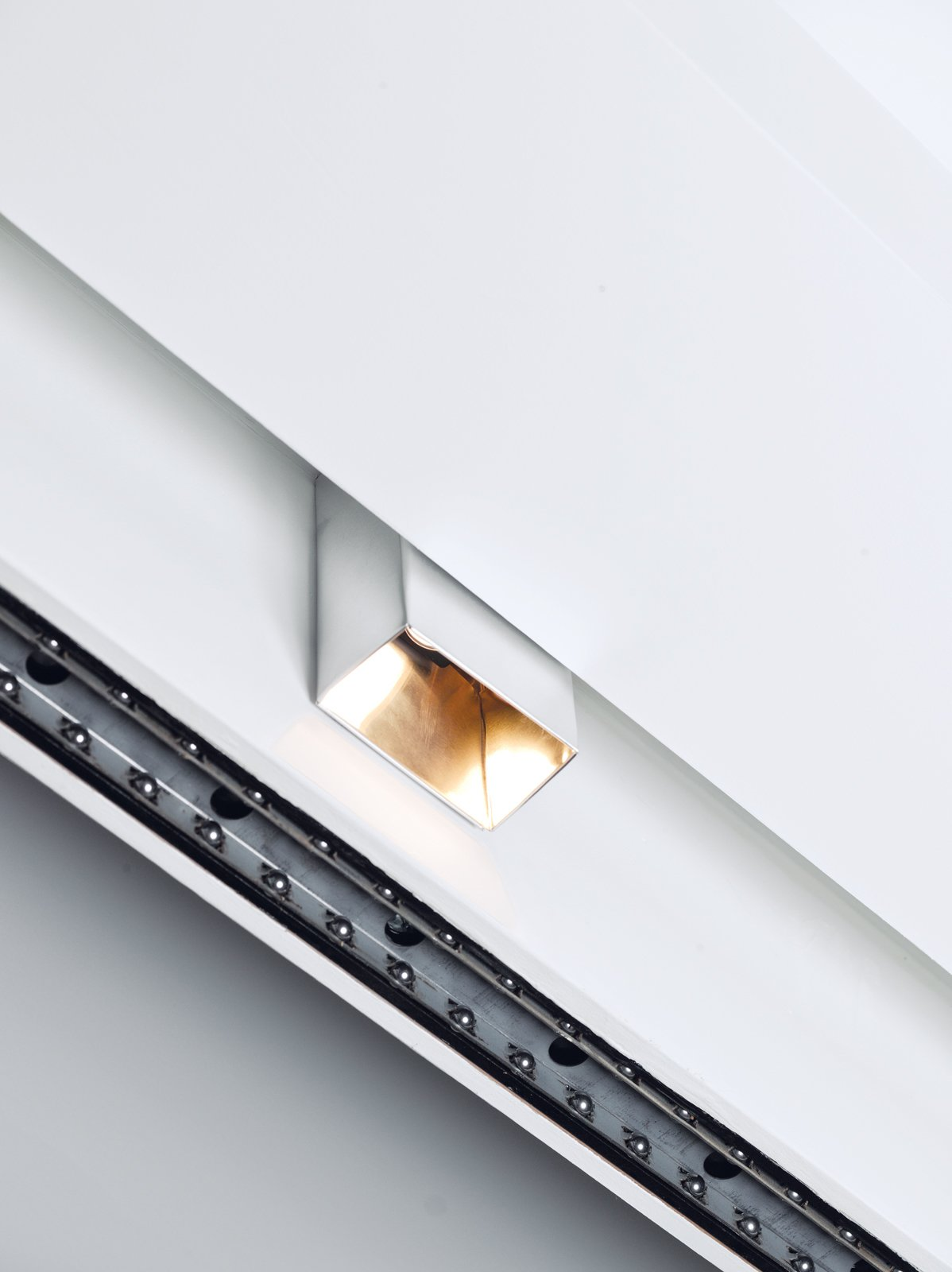 The couple really liked Prologue can lights by Kreon but couldn't afford them. So they bought aluminum sheets, sanded them, and folded them around standard track fixtures for a similar look. The total cost, including the transformer: about $40 per fixture.  Photo 13 of 14 in Stow Aways