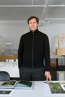 "Thomas Phifer stands in his west SoHo office and studio, with the firm's exquisitely crafted architectural models behind him. The room's all-white walls and ceiling are receptive to shadow and sunlight: ""I love turning out the lights here; you see the color of the walls changing all day long,"" says Phifer."