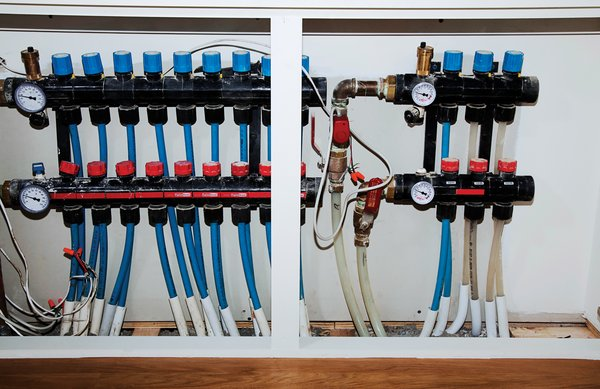 The radiant-heating system's pipes and gauges hide in a closet.