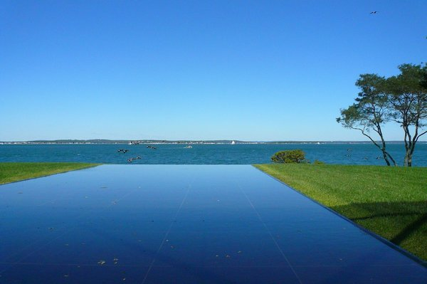 On one side of the house, a reflecting pool with an infinity edge seems to run right into the ocean.
