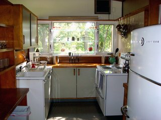 "The kitchen is one of the most unified spaces in the house, thanks to the appliances. ""Within a week of each other, we found the 1949 GE stove on E-Bay that matched the fridge,"" says Miller. ""They were the same model of appliances that were used in the exhibition house; they matched the pictures exactly. The owner even had the original instruction booklet and the appliances were in pristine condition. It was an amazing discovery."" Photo by Diana Budds."