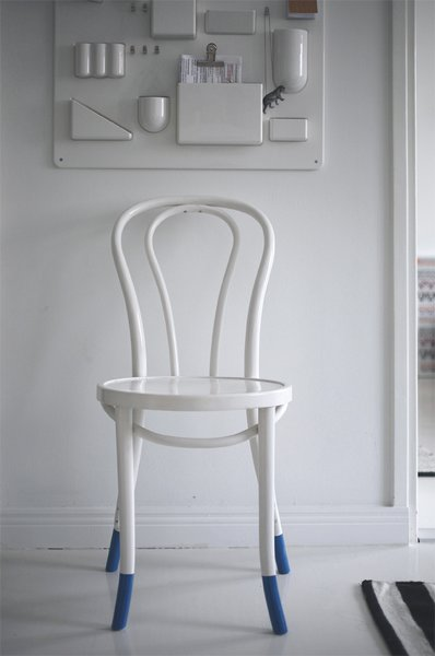 In the entryway, a plastic Uten.Silo organizer by Vitra shelters keys and other bits of potential clutter. A white-painted cafe chair suits the minimalist color scheme.