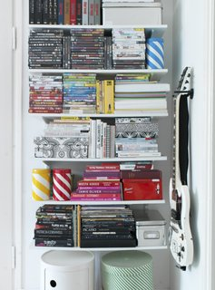 To keep her open storage neat, Susanna stacks and organizes her books and DVDs by size and by color.