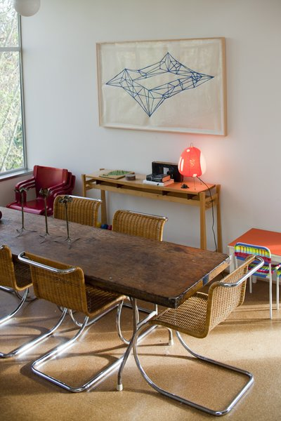 In the dining room, a painting by Victoria Haven hangs over a maple side table that Hale designed and built while in architecture school at the University of Washington. The dining table was a banquet table that Hale repurposed, and the Mies van der Rohe chairs were vintage store finds given to Hale and Edmonds as a housewarming gift.