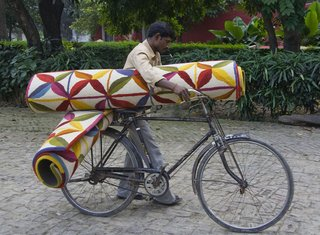 Nani Marquina - Photo 1 of 4 - Not sure how he's going to ride his bicycle with two rolled-up Kala rugs, but....