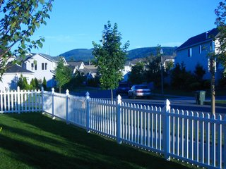 View from side yard. Corner lot, white picket fence, mountain view and streets lined with suburbia.