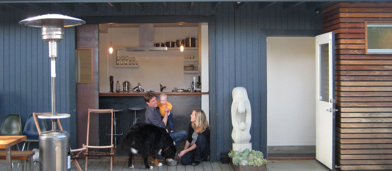 "Shoup, his wife, Taya, and daughter, Hannah, relax on the deck off the kitchen with their dog, Stella. ""For a high percentage of the year, we just roll open the door, and everybody hangs out in the kitchen, where we can keep an eye on Hannah,"" explains Shoup. ""There's kind of a leathery quality to it,"" he says of the door, which he fabricated of steel, with glass salvaged from an old sliding door. The sandstone sculpture is called ""Mother and Daughter."" Photo by Aya Brackett. Creative Re-Use in Oakland - Photo 4 of 11"