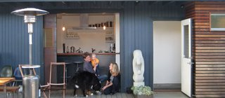 "Shoup, his wife, Taya, and daughter, Hannah, relax on the deck off the kitchen with their dog, Stella. ""For a high percentage of the year, we just roll open the door, and everybody hangs out in the kitchen, where we can keep an eye on Hannah,"" explains Shoup. ""There's kind of a leathery quality to it,"" he says of the door, which he fabricated of steel, with glass salvaged from an old sliding door. The sandstone sculpture is called ""Mother and Daughter."" Photo by Aya Brackett."