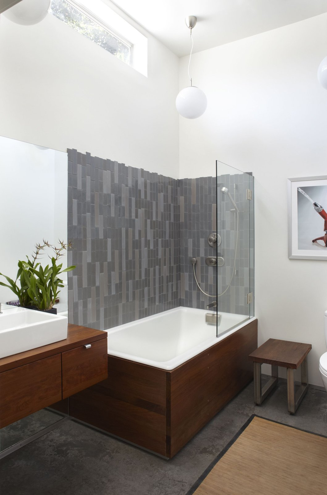 "Shoup accentuated the feeling of space in the master bath by opening it up to the full ceiling height. Ipe wood sheathes the sink and tub. ""The tile has the appearance of stranding to play off the bamboo in the bedroom,"" notes Shoup, who sourced the tile at Heath Ceramics' seconds warehouse. ""I pulled a bunch of their less-than-perfect tiles. They're a little bent, and the glazing is a bit off, but the lack of perfection actually serves us well."" The light fixtures are from Ikea. Photo by building Lab inc."