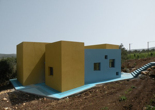 The house sits on a slope, atop blue concrete and ceramic tiles. A set of web-shaped stairs (right) flow like a waterfall onto the blue floor.<br><br>Photo courtesy <br><br>Z-A Studio.