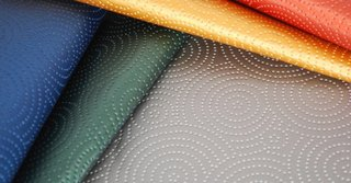 Kravet's Sta-Kleen performance fabric is a throwback to the 1950s formaldehyde resin fabrics, with its faux leather feel, raised circular designs and availability in five bright hues.