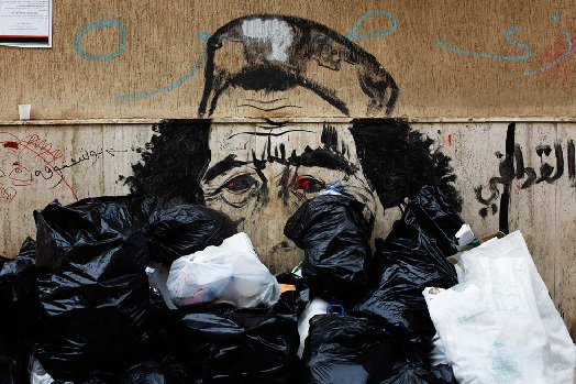 "Photojournalist Finbarr O'Reilly documented anti-Qaddafi sentiments strewn across walls and on posters in Libya. Photo via Caricaturing-qaddafi"">The New York Times."
