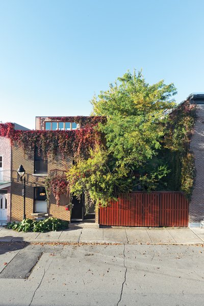 Greenery bursts out to the street from the side yard of Paul Bernier and Joëlle Thibault's home.