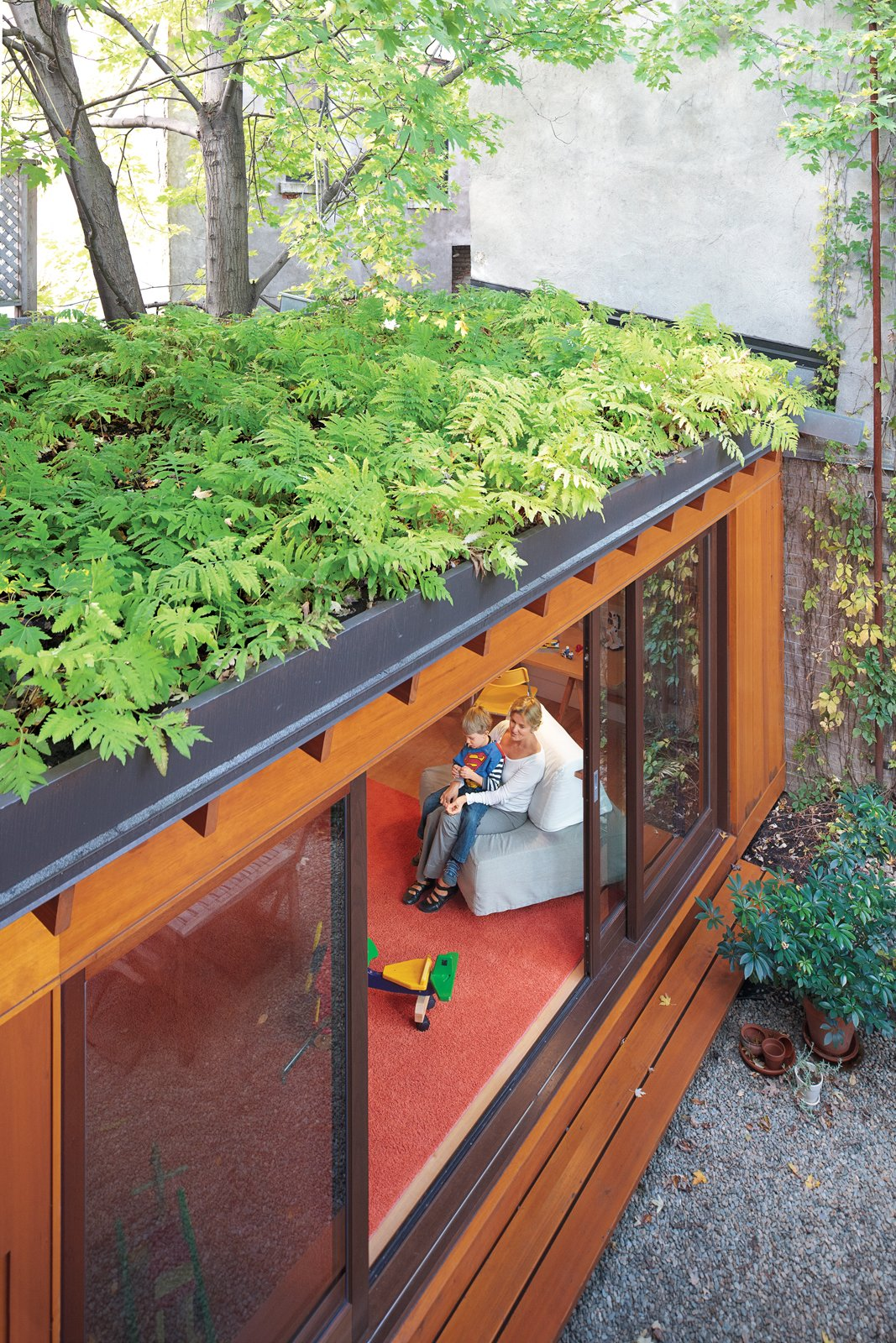 A small, single-story addition to the row house adds a playroom without eating up too much outdoor space. A green roof also helps makes up for lost garden beds, while creating attractive, leafy views from the second and third floors. In summer, when the sliding doors are left wide open, indoor and outdoor spaces blend together.  The Most Popular Homes in Dwell: 81-100 by Diana Budds from Separate Boîte Equal