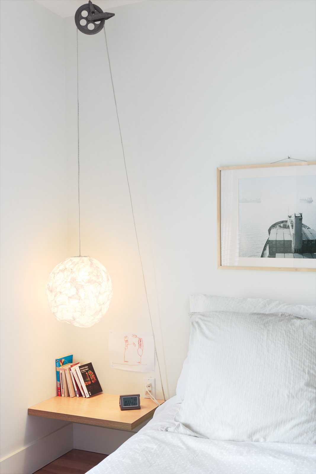 """Reel Simple  For a simple, low-cost bedside reading light with a dash of industrial style, Bernier ran a standard-issue cord set through a vintage clothesline pulley, which he picked up at a flea market, on Thibault's side of the bed. """"If she ever wants it to be higher, she can easily adjust it,"""" he says.  Bedrooms by Dwell from Separate Boîte Equal"""