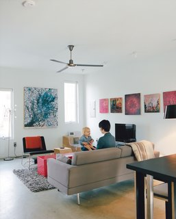 Courtney and Teague play in the living room opposite a Perch lounge designed by Eric Pfeiffer for Offi. The paintings behind the TV are by artist Chris Clark.