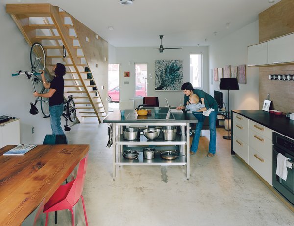 The long, rectangular bottom floor is one uninterrupted space. Bikes live beneath the stairs, and the kitchen island is a center of activity. The dining table was made by Bench Dog Design and the Real Good chairs are by Blu Dot. An inexpensive fan by Emerson and exposed CFLs are smart, low-cost options for the ceiling.