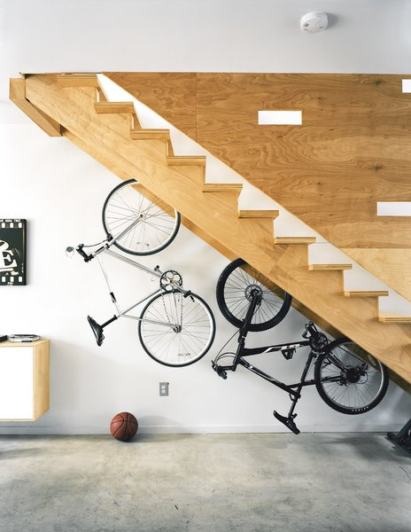 More adult playthings, like this pair of bikes live under the stairs, whose cutouts break up the plane of plywood and double as peepholes for kids at play.