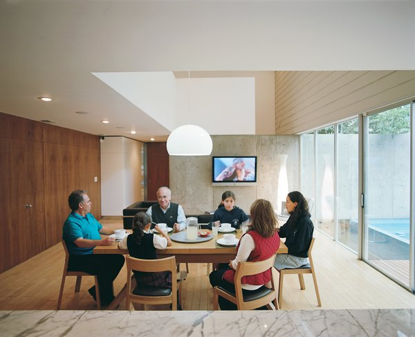 Marco Becerril, at the left end of the table, presides over his extended family in the double-height dining area.