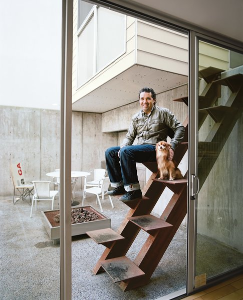 The architect Jorge Gracia sits on his handiwork, an unusual custom-made Cor-Ten stair leading from the courtyard to the guesthouse.