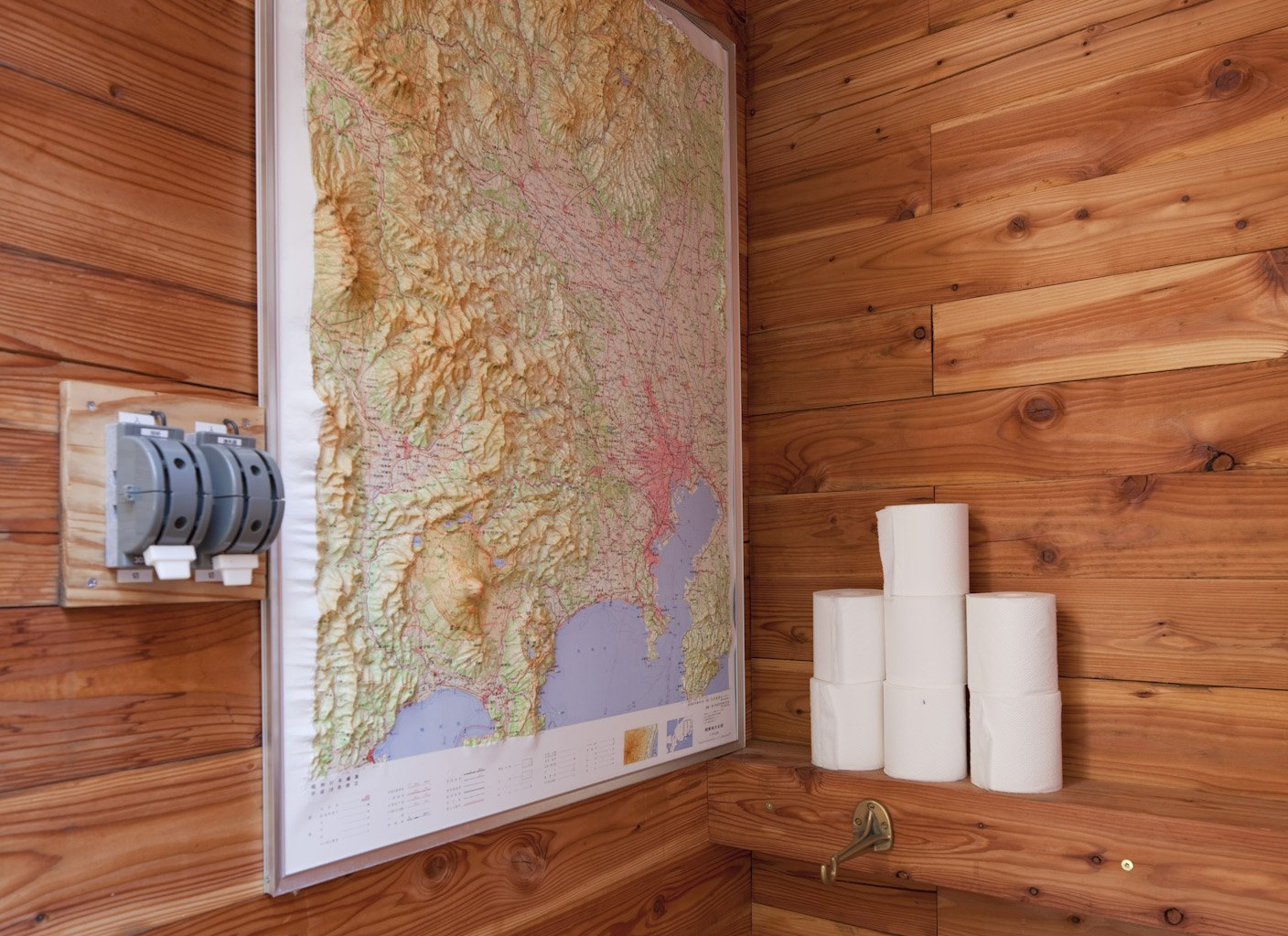 A peek inside the bathroom, where a raised topographic map doubles as reading material and travel inspiration.  Photo 20 of 28 in A Platform for Living