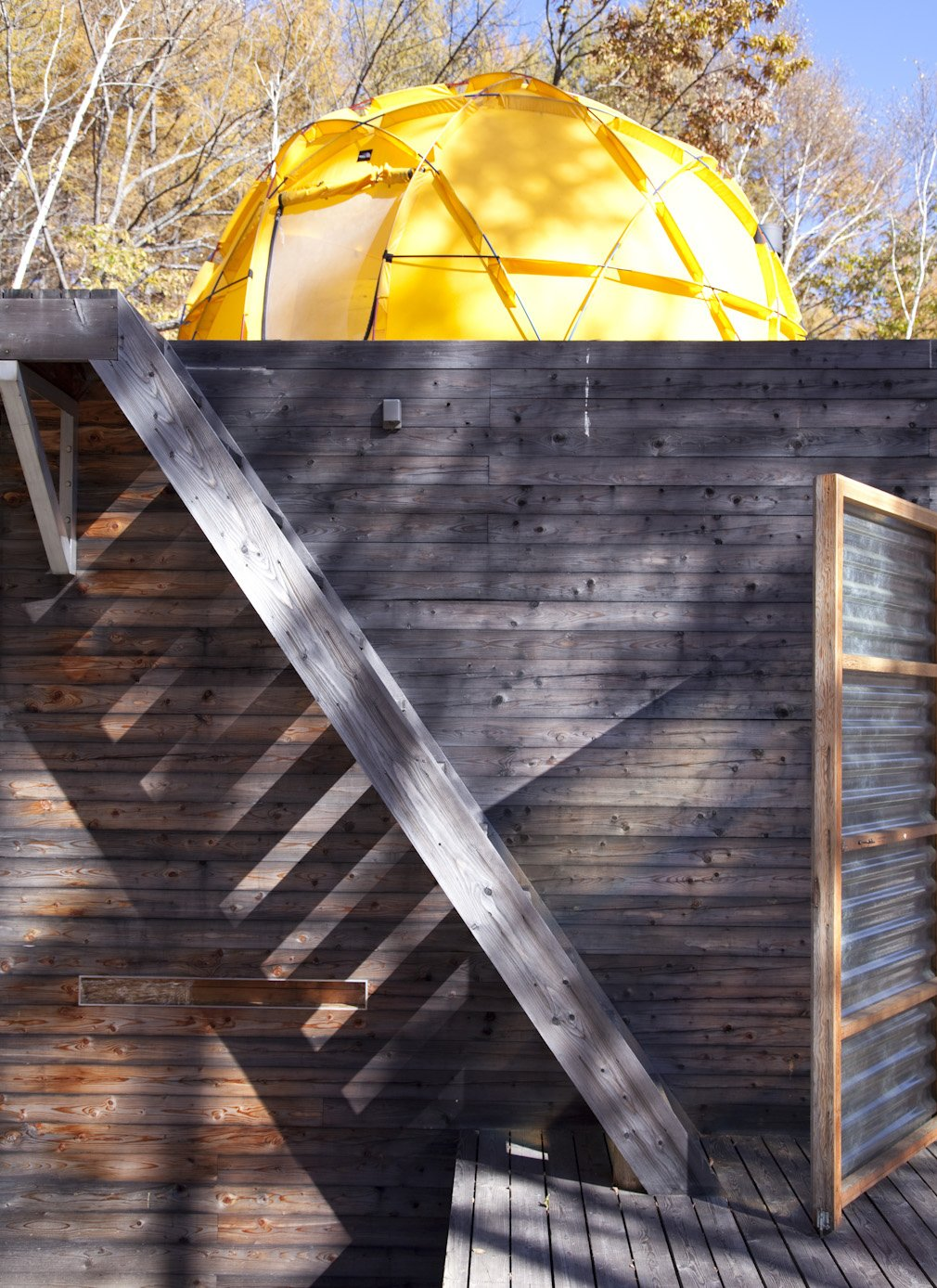 The yellow North Face tent looms over the top of the main building.  Photo 21 of 28 in A Platform for Living