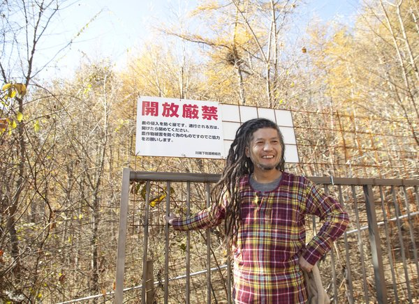 The dreadlocked Ishii Hideaki grins at the gate to the Kobayashi's property.