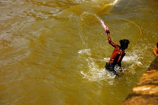 Touring India - Photo 21 of 27 - During the festival of Holi, Mumbai's inhabitants take to the streets and paint each other. This kid had enough and jumped in the harbor to wash himself clean.