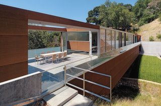 Stanley Saitowitz's Bridge House was built atop a challenging parcel. The rectangular structure spans a small valley created by a creek.
