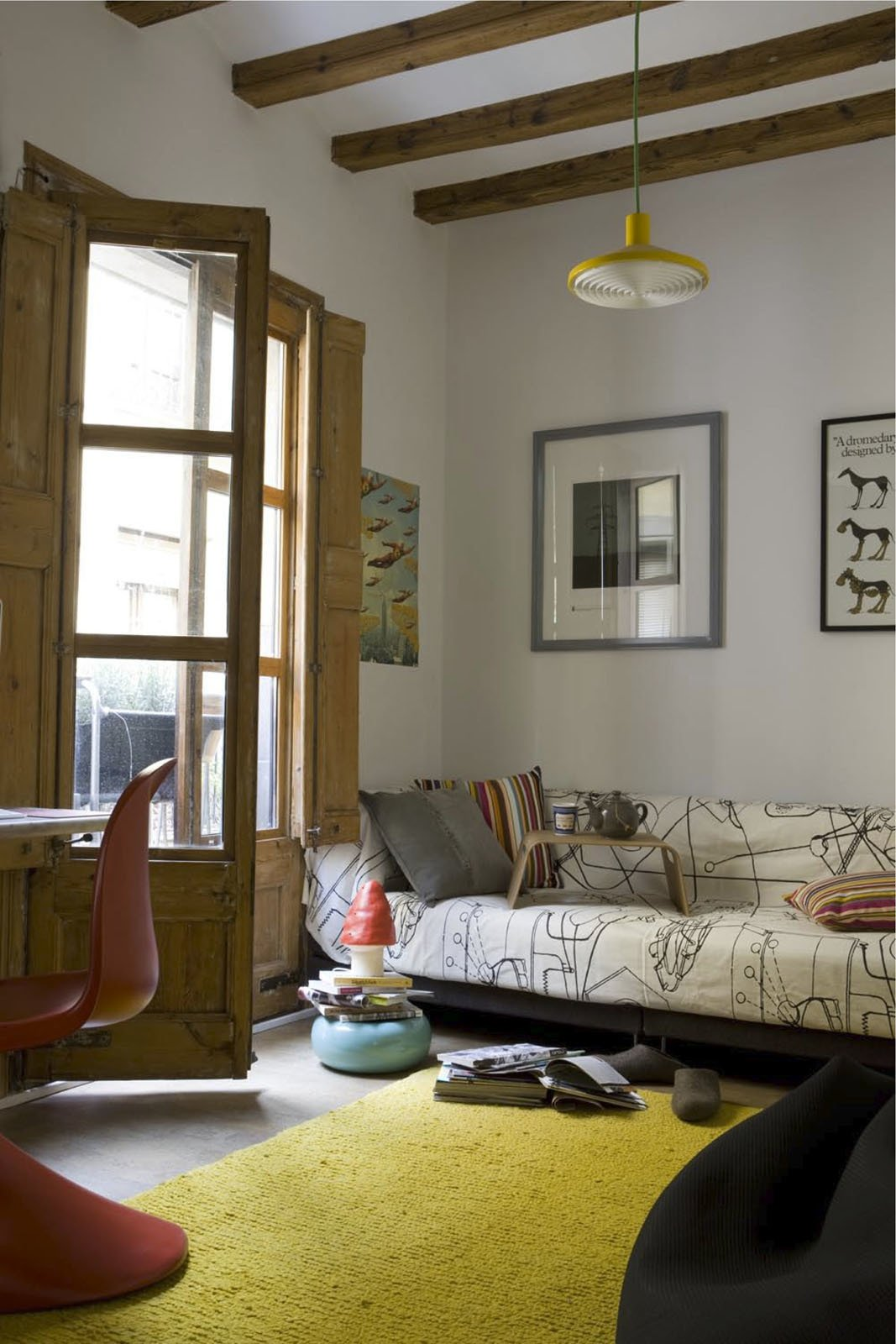 Wishing to avoid using harsh chemicals, the couple had the 18th-century beams and French doors in the living room and elsewhere sandblasted to rid them of woodlice. The rug, by Nani Marquina, is renewable and biodegradable as well as ethically produced.  Photo 9 of 10 in 10 Modern Renovations to Homes in Spain from Green Living in Barcelona