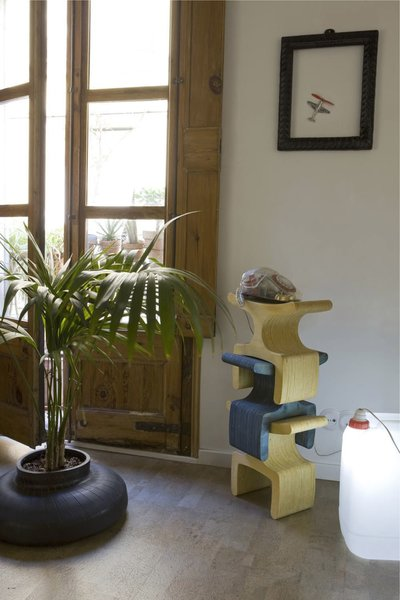 "An old tire finds new life as a planter, while the Enzo Stool by Ryan Frank serves as a telephone stand. The lamp at right was crafted using a discarded plastic container. ""We like objects made from few and easily identifiable materials, to ensure that they can either be industrially recycled or returned to the earth at the end of their lives,"" says Scholtus."