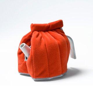 A bright orange tea cosy by Jongerius Lab.