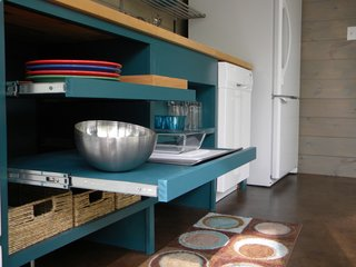 7 Surprising Shelving Ideas For the Creative Organizer - Photo 2 of 7 - Made for easy reaching, these open pull-out shelves are in an ADA-compliant kitchen in a guesthouse designed by architecture firm Best & Associates. Although the shelves were designed without doors, they were painted inside and out with a turquoise paint for a uniform, finished look, and the sliding shelves mean that every inch can be accessed, even the very back of the shelves.