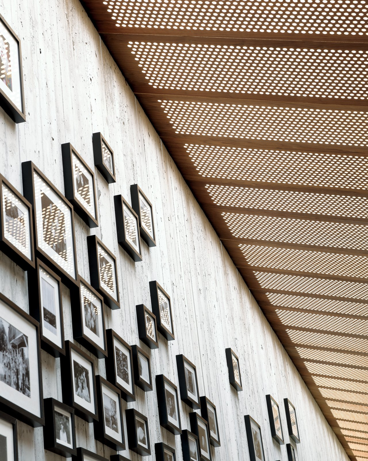 Framed family photos hang, clustered and skylit, in the corridor. Tagged: Hallway. 23.2 House by Jordan Kushins