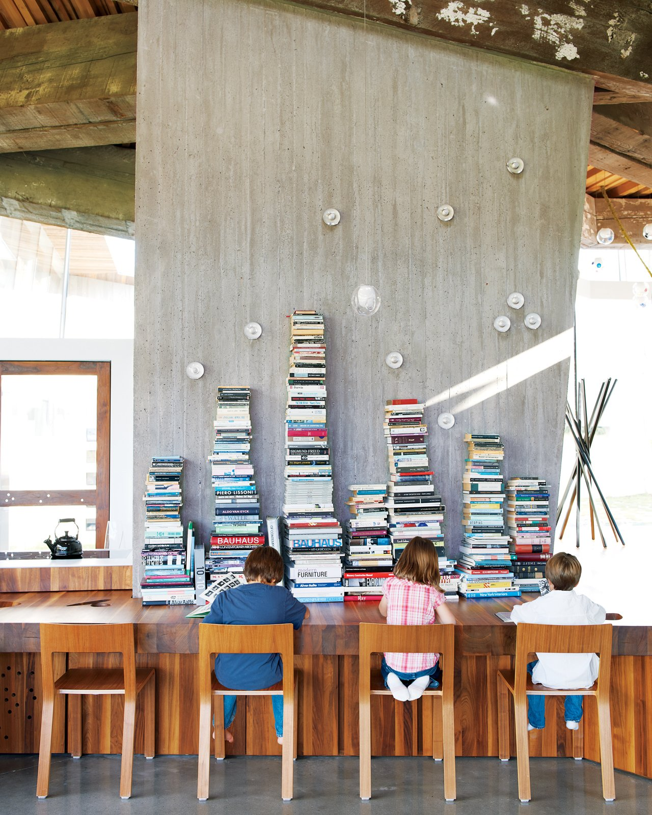 Impromptu reading time in the open-plan kitchen is encouraged. Tagged: Dining Room, Table, Concrete Floor, and Chair.  23.2 House by Jordan Kushins