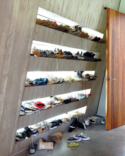 Just off an internal courtyard, a mudroom provides a prime place to keep sneakers. Each family member has their own shelf, backlit by windows that illuminate every pair. Photo 10 of 23.2 House modern home