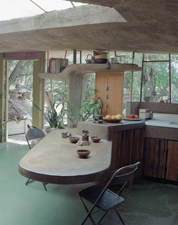 10 Works of Architecture That Reveal the Acrobatic Wonders of Concrete - Photo 9 of 10 - At a smaller scale than an entire building, a concrete, cantilevered countertop and table extends both inside and outside at the Arizona home of Italian architect Paolo Soleri. A sculptural shelf frames the window and door beyond, with rounded edges for a soft, supple feel.