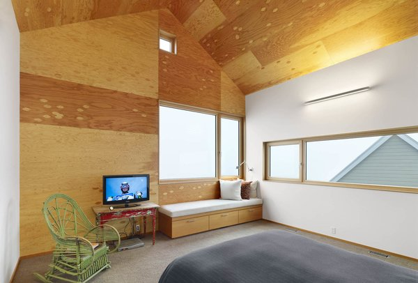 Inside the master bedroom, the juxtaposition of old and new is pronounced. Wooden furniture sits next to a streamlined built-in bench. The wood-framed windows open up to views of the gabled roof. Photo 6 of The Farm modern home