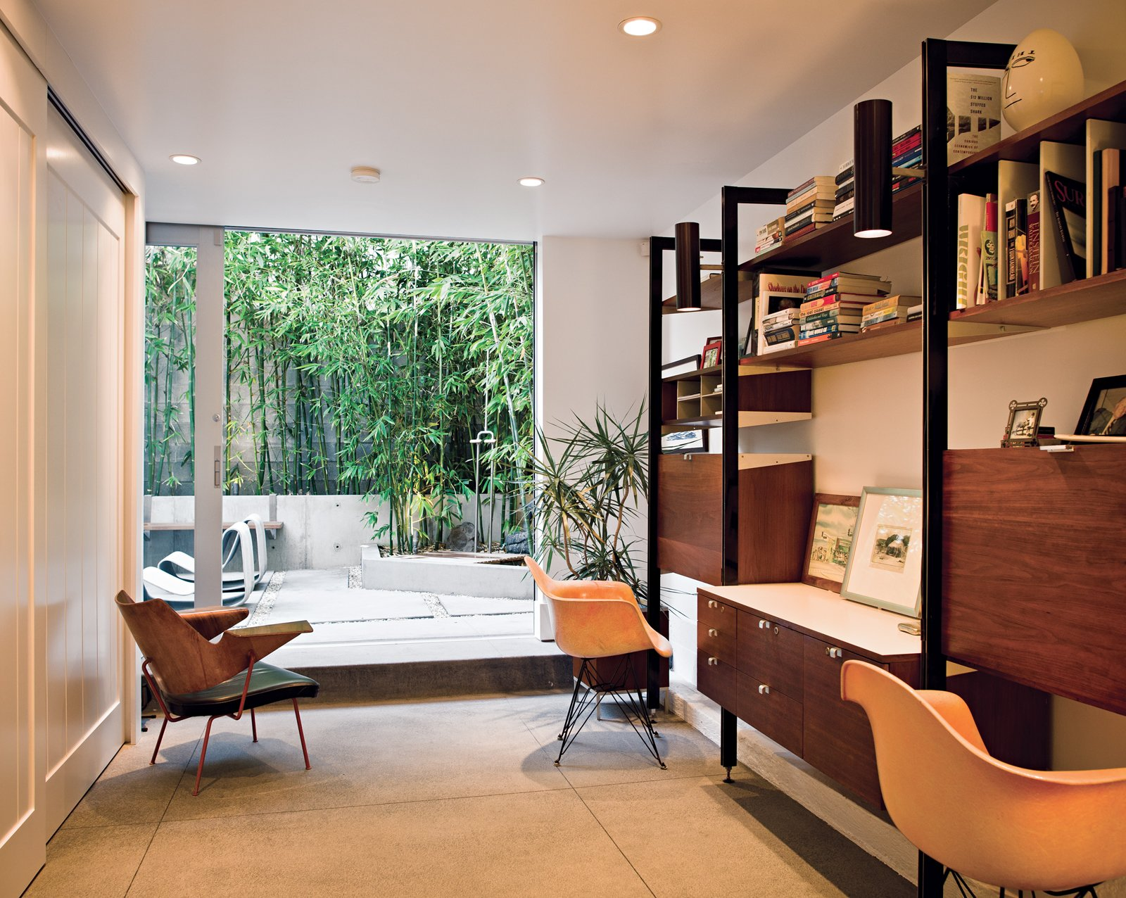 A bentwood Robin Day chair keeps the Herman Miller classics company. Through the office's door, nestled in the bamboo grove, is an outdoor shower, fashioned after those found in San Onofre, farther south. Tagged: Office, Study, Desk, and Chair.  Photo 11 of 18 in Less is More in this Manhattan Beach Bungalow