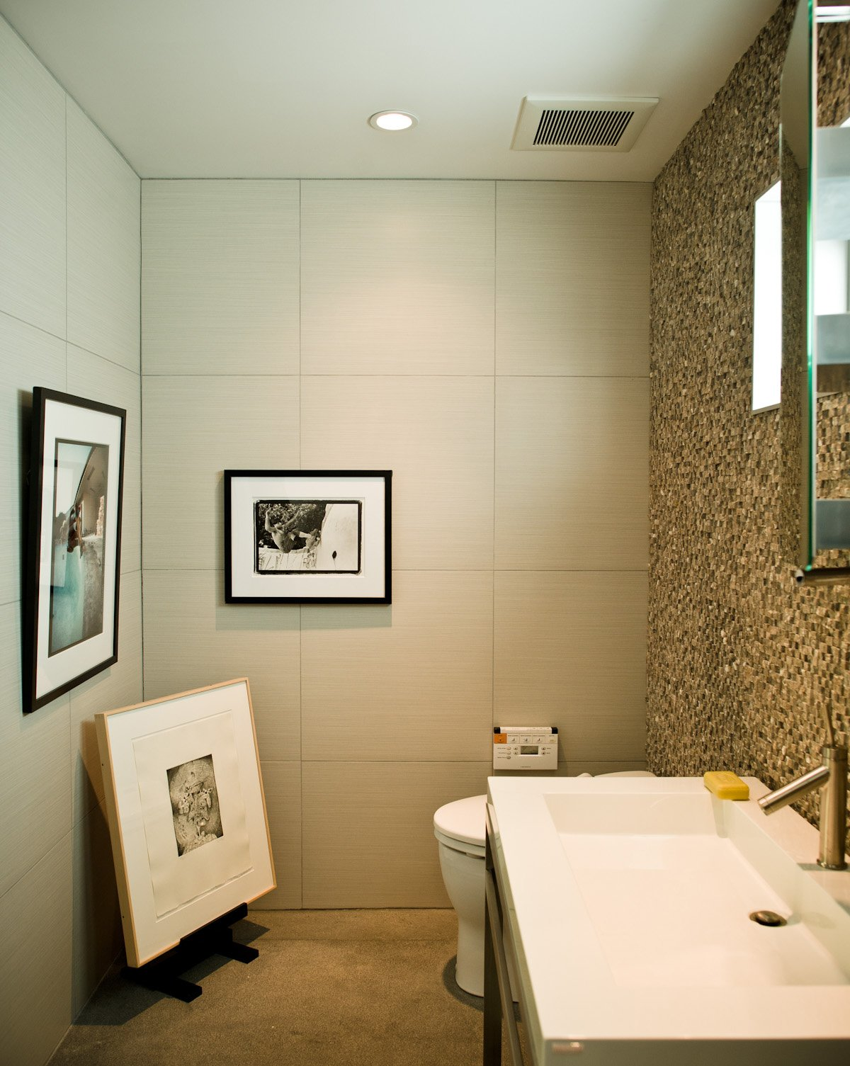 No room in the house is free from Jacobson's keen curatorial eye. The office bathroom is adorned with an original Glen E. Friedman image of skate legend Tony Alva (across from toilet) and a picture of Nathan Fletcher by Mark Oblow (adjacent). Framed on the floor is a George Condo illustration.  Photo 15 of 18 in Less is More in this Manhattan Beach Bungalow