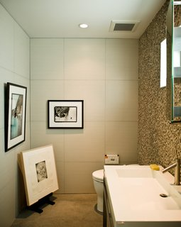 Less is More in this Manhattan Beach Bungalow - Photo 15 of 18 - No room in the house is free from Jacobson's keen curatorial eye. The office bathroom is adorned with an original Glen E. Friedman image of skate legend Tony Alva (across from toilet) and a picture of Nathan Fletcher by Mark Oblow (adjacent). Framed on the floor is a George Condo illustration.