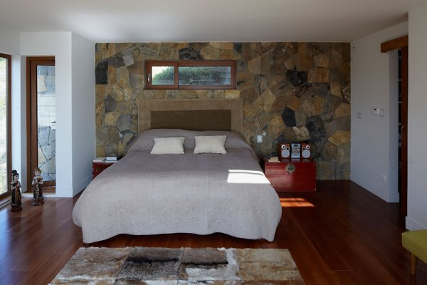 From her bedroom on the lower level, Schneider can walk out onto her balcony and take in the spectacular views of the Pacific Ocean. The wall behind the bed is the thermal-mass wall that provides heat throughout the night.