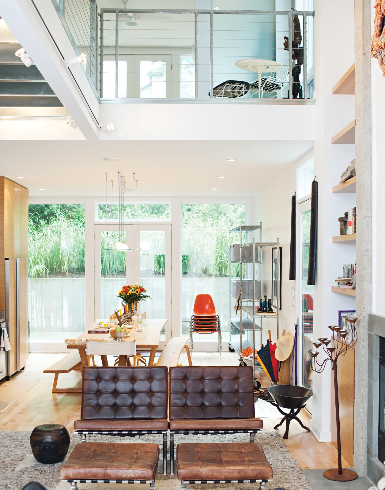 To create a sense of luxury on a budget, the architect ran a thin concrete border along either side of the fireplace flue and flanked it with floor-to-ceiling bookshelves. The second story has two lofts joined by a steel bridge. Tagged: Living Room, Light Hardwood Floor, Rug Floor, Standard Layout Fireplace, Bench, Chair, End Tables, Ottomans, Shelves, Storage, and Table.  Photo 2 of 25 in Come Sail Away