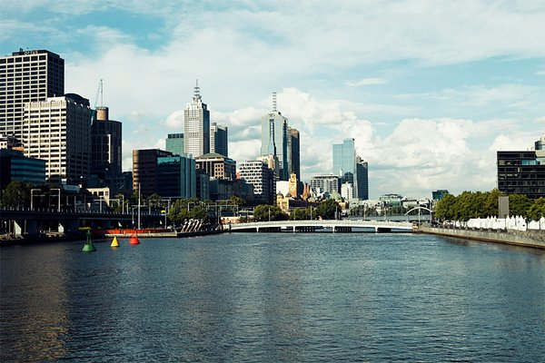 Looking east from the Kings Way Bridge over the Yarra you can see the yellow tower of Flinders Street Station and the points of St. Paul's Cathedral beyond.