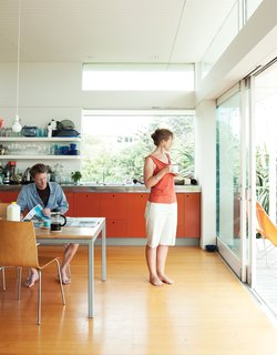 Bach to the Beach - Photo 2 of 30 - The bach was designed with a combined open-plan kitchen, living room, and dining area, for which Gerald designed a dining table that seats ten. Bare bulbs, open shelves, and bright orange MDF cabinets in the kitchen maintain the low-key vibe.