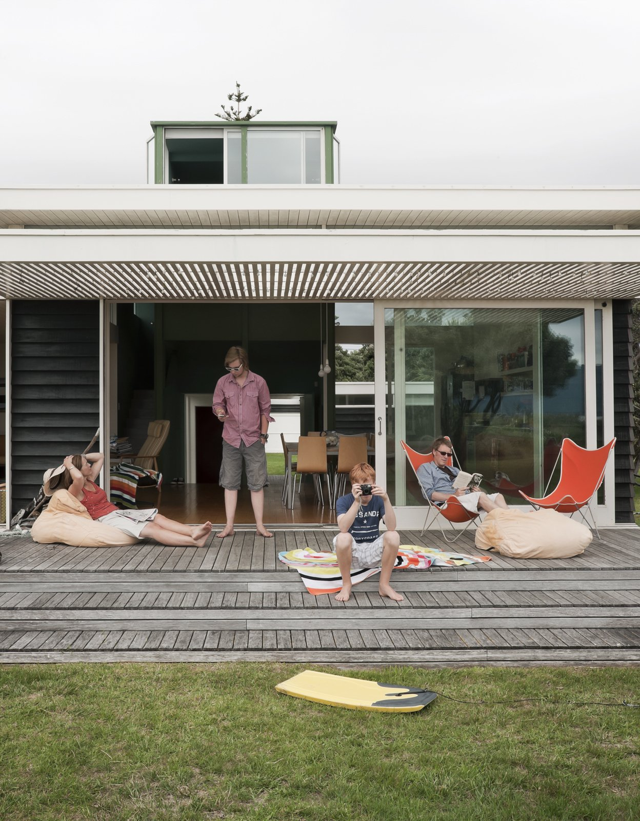 The family spends summers and school vacations at the bach. New Zealand's relatively mild winters mean they use the house year-round. Tagged: Outdoor, Grass, Wood Patio, Porch, Deck, and Small Patio, Porch, Deck.  Vacation Homes by Brandi Andres from Bach to the Beach