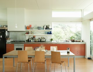 Bach to the Beach - Photo 17 of 30 - The orange-painted MDF cabinets add a pop of color to the sun-washed kitchen.