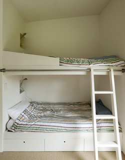 In the boys' room, a rolling ladder provides access to the top bunk.