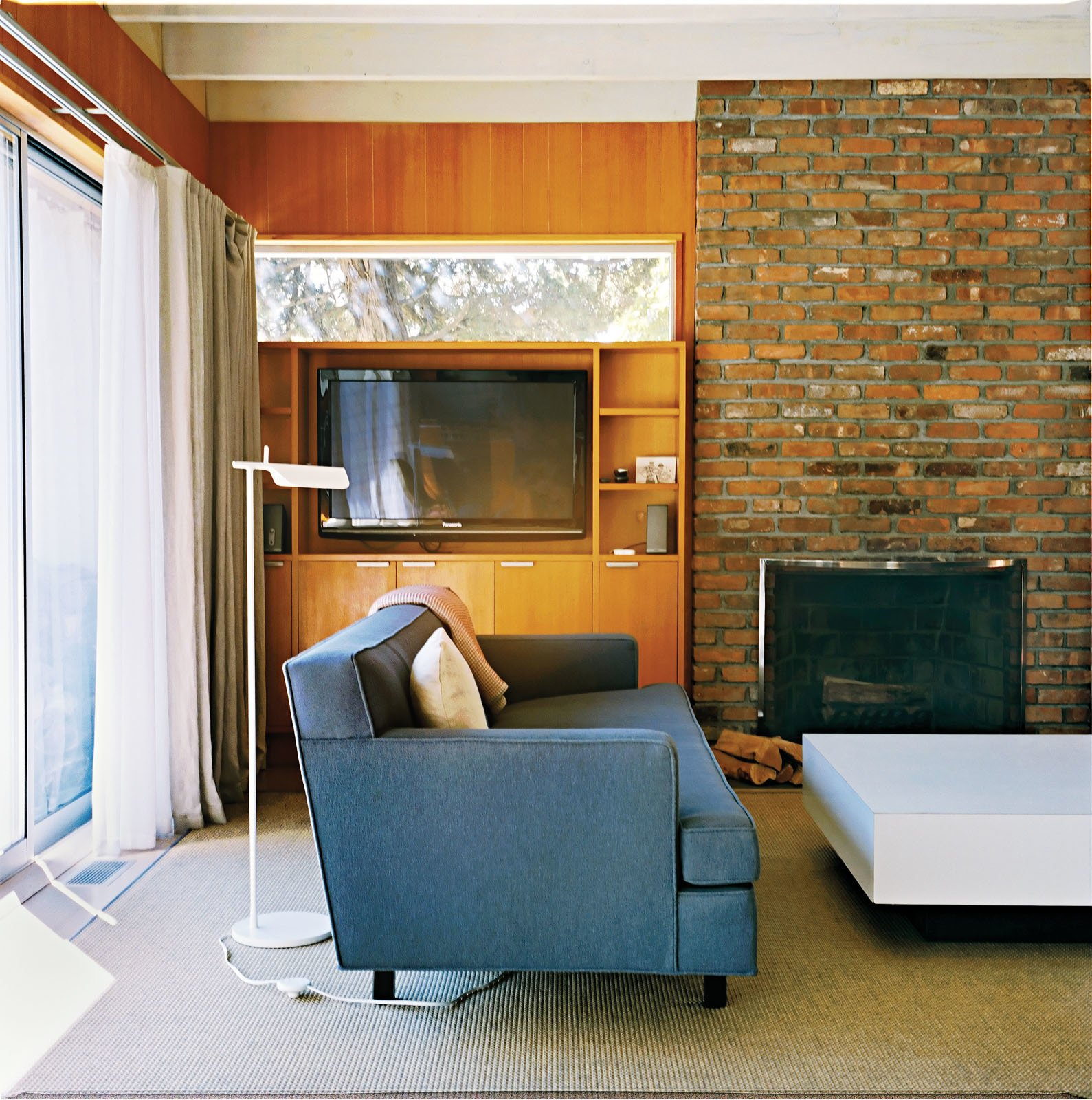 A Tab F1 floor lamp from Flos stands behind the Edward Wormley–designed Dunbar sofa. Tagged: Living Room, Standard Layout Fireplace, Wood Burning Fireplace, Floor Lighting, and Sofa.  Photo 2 of 12 in Long Island Found
